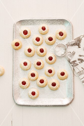 Husarenkrapferln (shortbread jam biscuits) with icing sugar on a baking tray
