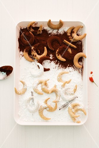 Vanilla crescent biscuits with icing sugar and cocoa powder (seen from above)