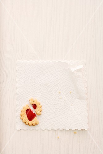 A broken jam biscuit on a doily (seen from above)