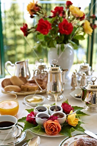 A table laid for breakfast with pots of jam and silver jugs with a bunch of flowers in the background (Villa Cimbrone Hotel)