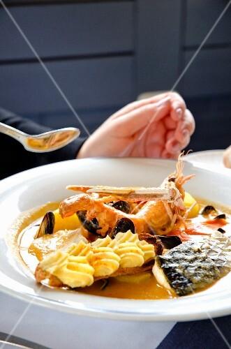 A person eating bouillabaisse