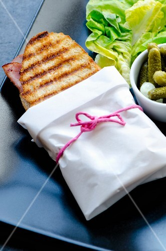 A ham and cheese panini wrapped in paper