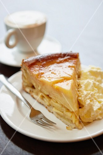 A slice of apple pie with cream served with coffee