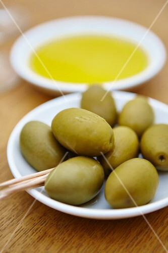 Green olives with wooden sticks on a plate