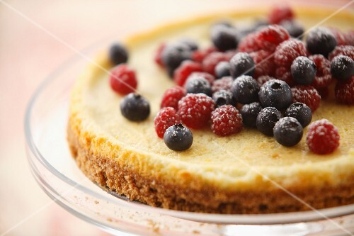A cheesecake with raspberries and blueberries