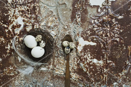 An Easter nest with eggs and feathers on an antique metal surface