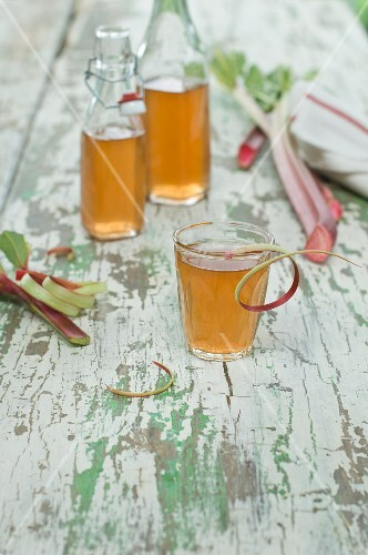 Homemade rhubarb juice in a glass and in bottles