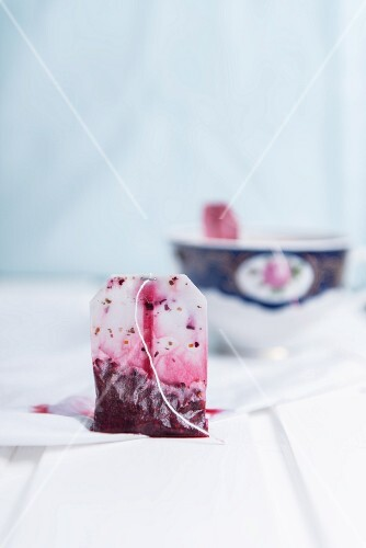 A used fruit tea bag with a porcelain cup in the background