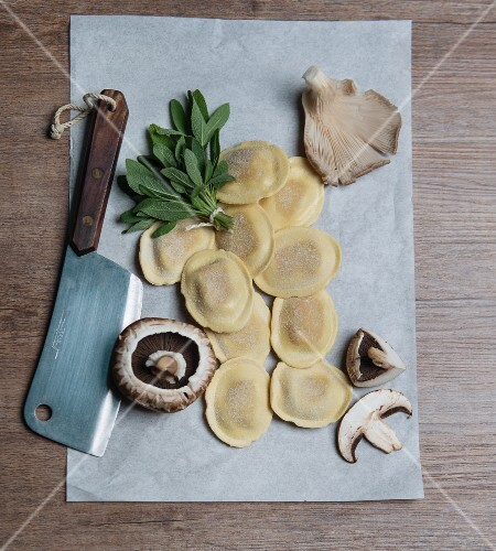 An arrangement of ingredients with ravioli, sage and mushrooms