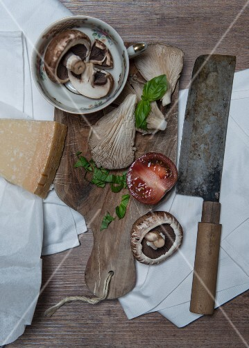 An arrangement of ingredients with mushrooms, tomatoes, Parmesan and Basil