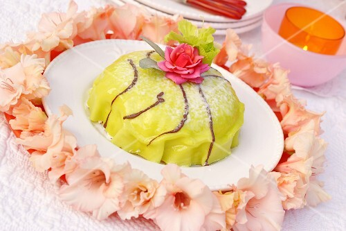 A mini cake decorated with roses and gladioli