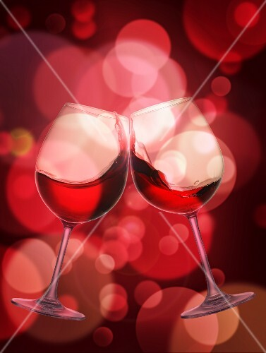 Two glasses of red wine being chinked