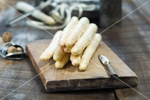 Fresh white asparagus on a chopping board next to a nutmeg grater with nutmegs