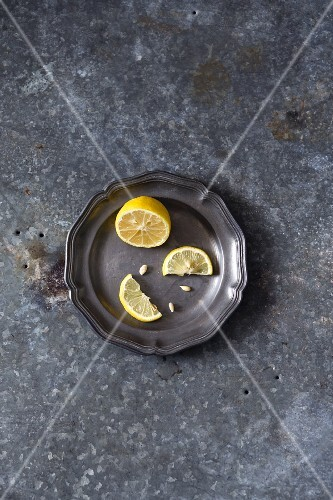 A lemon half and a halved lemon slice on a metal plate (seen from above)