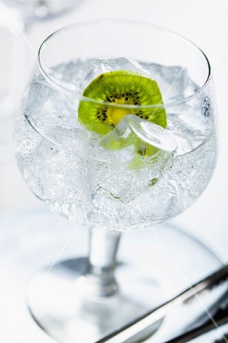 A gin and tonic with ice cubes and a slice of kiwi
