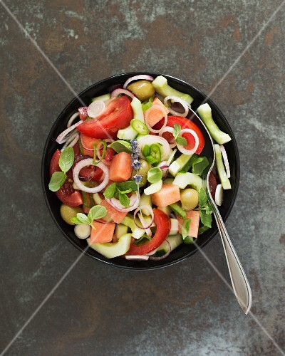 A summer salad with tomatoes, cucumber, melon, olives and herbs