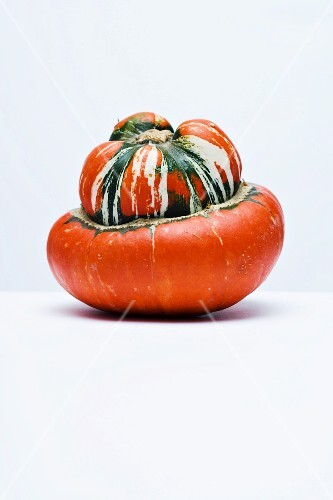 A turban squash on a white surface