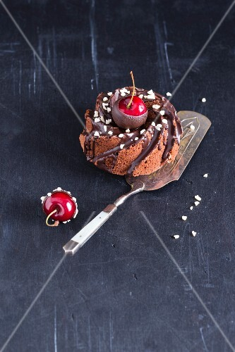 A mini cakes with chocolate glaze, almonds and chocolate-coated cherries