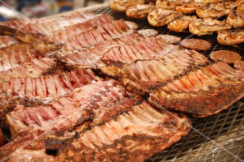 Pork ribs, chicken and burgers cooking on large charcoal grill at a market