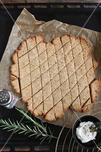 Gluten-free, diamond-shaped crackers with rosemary and sesame seeds on a baking tray with a bowl of dip and a sprig of rosemary