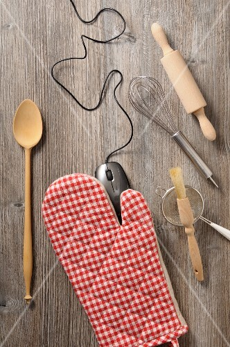 Kitchen utensils and a computer mouse on a wooden surface