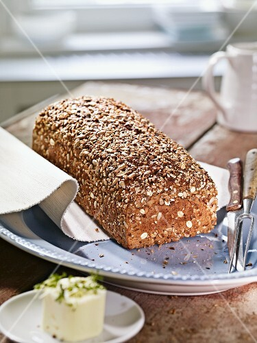 A whole loaf of wholemeal rye bread with seeds on a plate