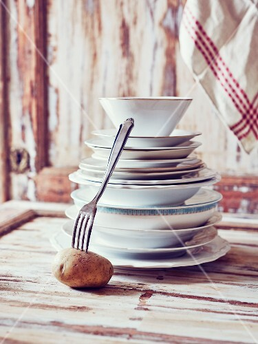 Still-life arrangement of crockery, fork and potato