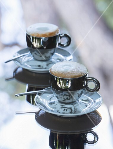 Cappuccino in designer cups on table with mirrored top