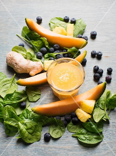 Melon and ginger smoothie surrounded by spinach leaves, blueberries and melon slices