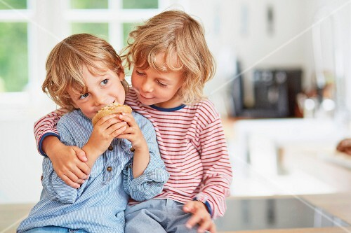 Little boys sitting at a kitchen counter with a muffin