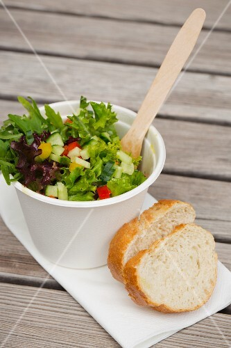 A salad in a take-away cup with a wooden fork and baguette slices
