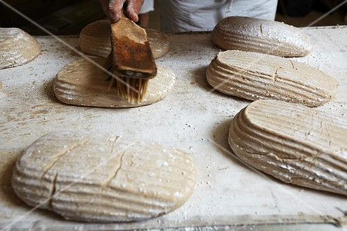 Loaves of unbaked bread being brushed with water