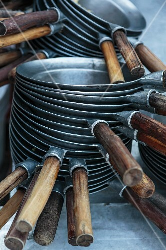 A stack of frying pans in a restaurant kitchen (Thailand)