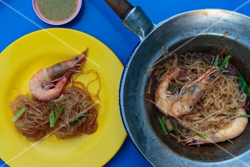 Fried prawns with vermicelli in a pan and on a plate (Thailand)