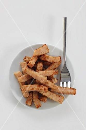 Fried chicken strips on a plate on a white surface