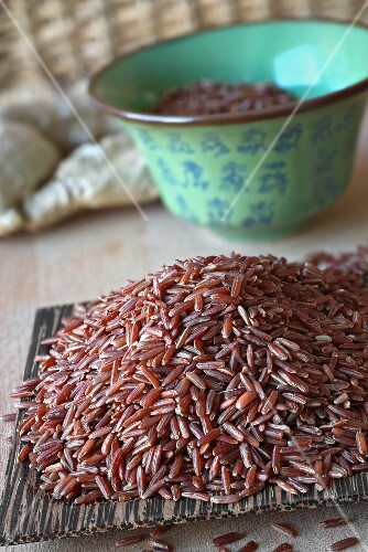 Red rice on a wooden coconut dish (Asia)