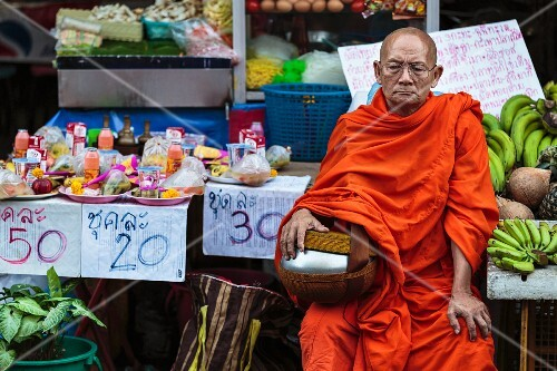 A Buddhist monk sitting at a market stall begging for alms (Thailand)