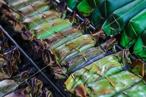 Stuff banana leaf parcels on a barbecue (Thailand)