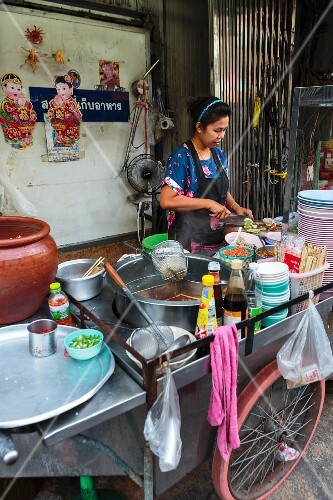 An oriental woman making food at a mobile street kitchen (Thailand)