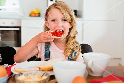 A little girl eating bread and jam at a kitchen table