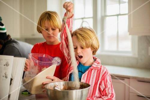 Brothers pouring flour into mixing bowl in a kitchen