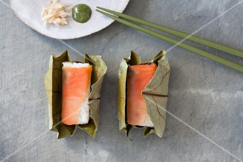 Salmon sushi with ginger strips and wasabi wrapped in a leaf