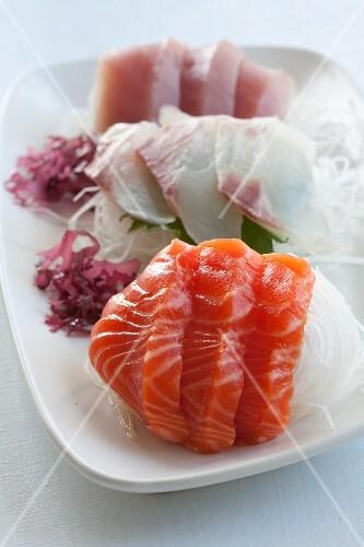 Sashimi on strips of radish with seaweed