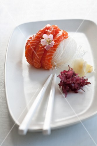 Salmon sashimi on radish strips with a cherry flower