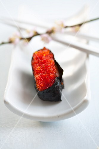 Sushi with salmon caviar and a sprig of cherry blossoms