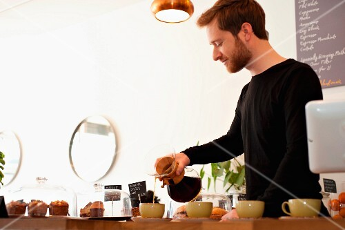 A young cafe worker pouring filter coffee into cups