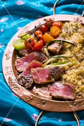 Fried tuna with garam masala served with bulgur and tomatoes