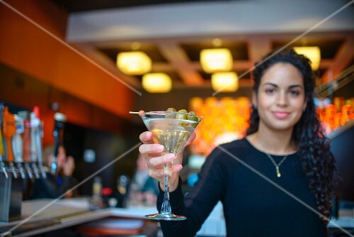 A young woman serving a cocktail