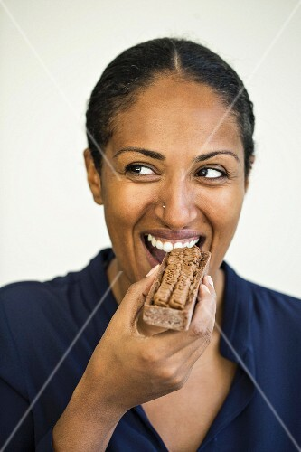 A woman eating a chocolate mousse tart