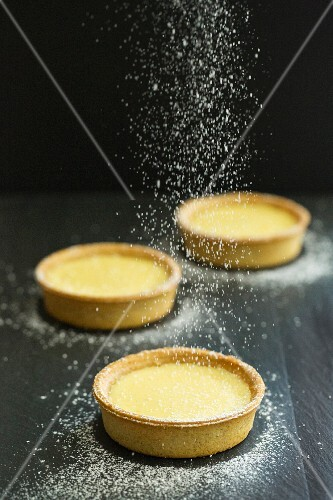 Lemon tarts being dusted with icing sugar